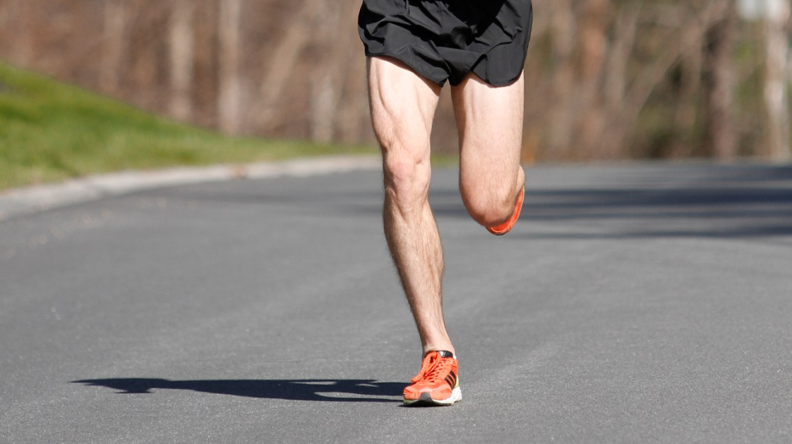 Lower body image of a man in running shorts with well-defined quadriceps, jogging down a wooded street.