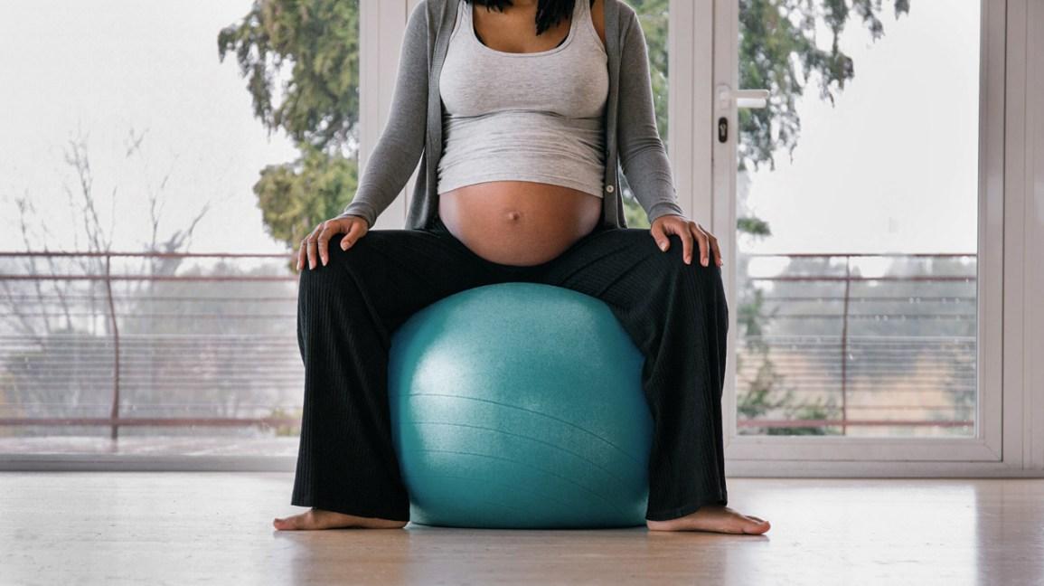 Mulher grávida sentada na bola de exercícios