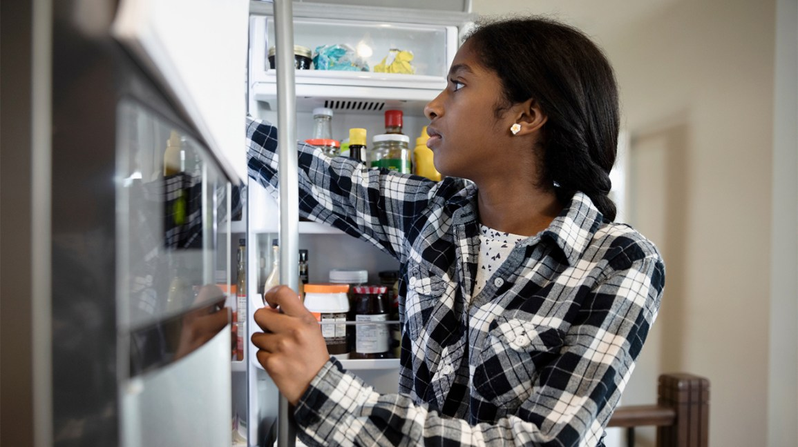 teen girl reaches into a refrigerator that is filled with food