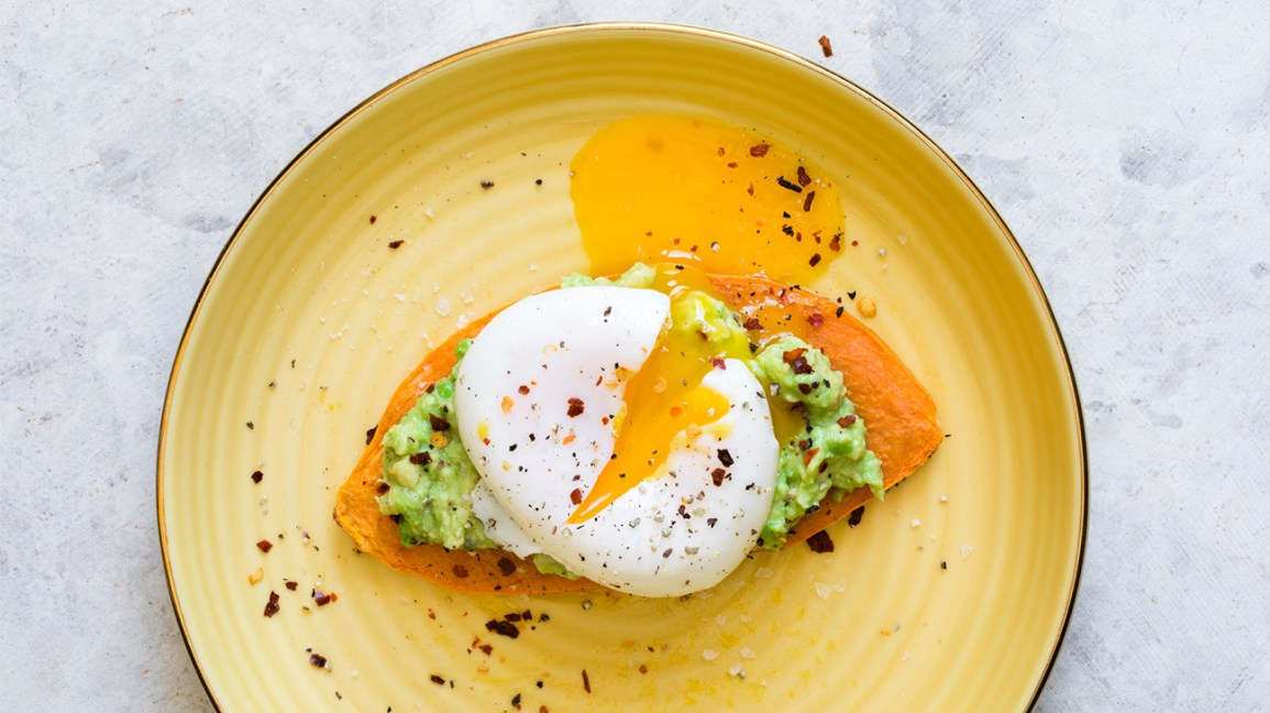 sweet potato toast topped with a poached egg, avocado, and spices