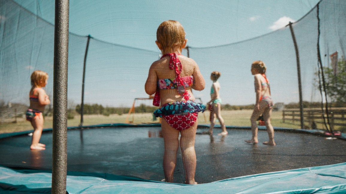 Toddler watching kids play on trampoline