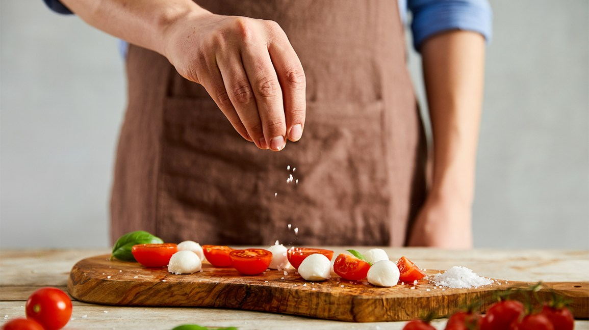 Chef salting tomato mozzarella dish