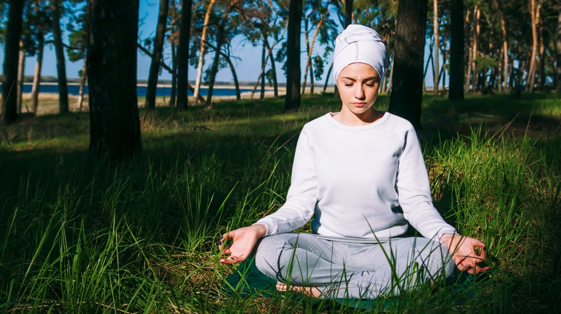 woman practicing kundalini meditation in the grass