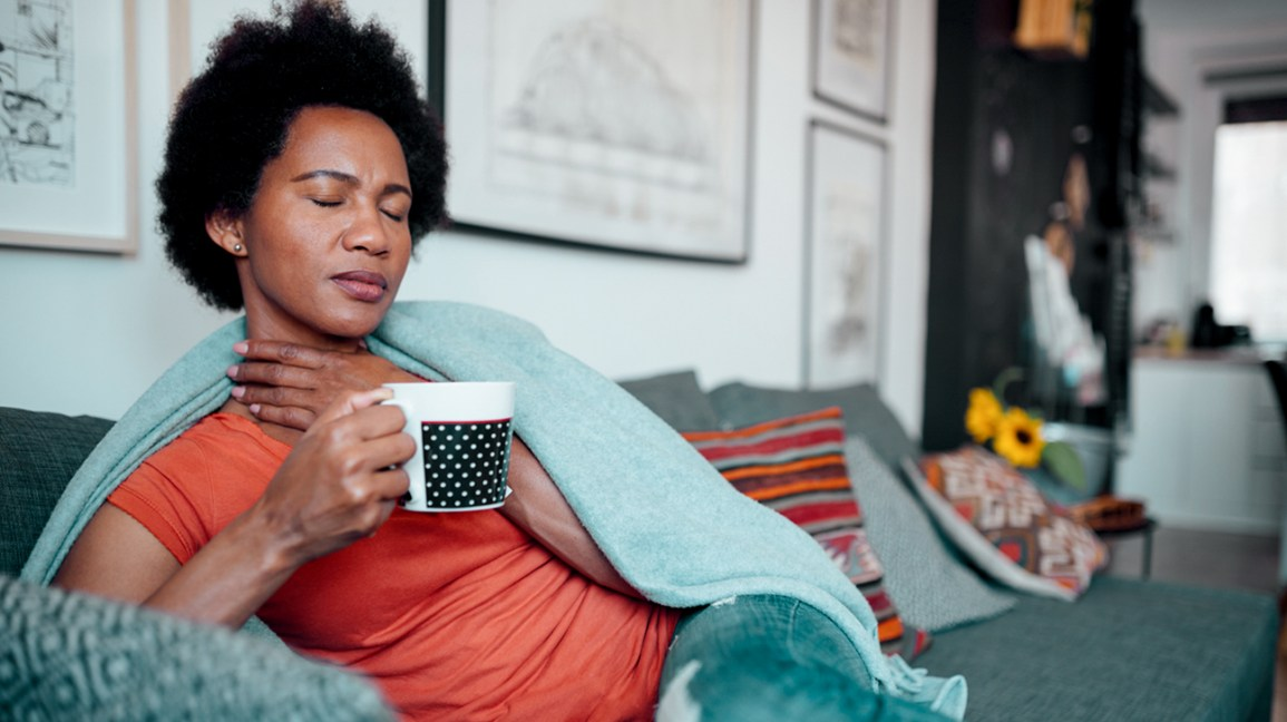 A woman who is feeling ill, sits on a couch with a blanket around her, while touching her sore throat.