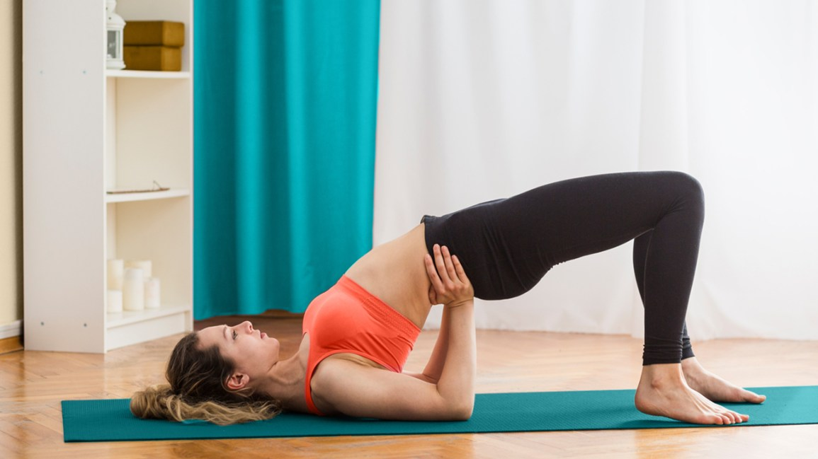 person wearing a red-orange crop top and black leggings performing a hip thrust on a teal exercise mat