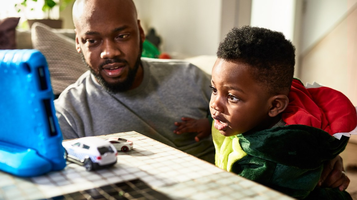 A father helps his young son communicate with the help of an electronic communication board.