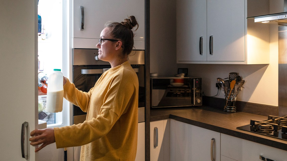 A woman stands in front of a refrigerator in her kitchen holding a container of milk in her hand.