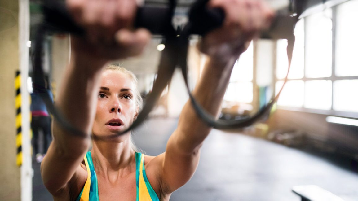 person wearing a yellow and teal tank top reach their arms forward to grasp two TRX straps