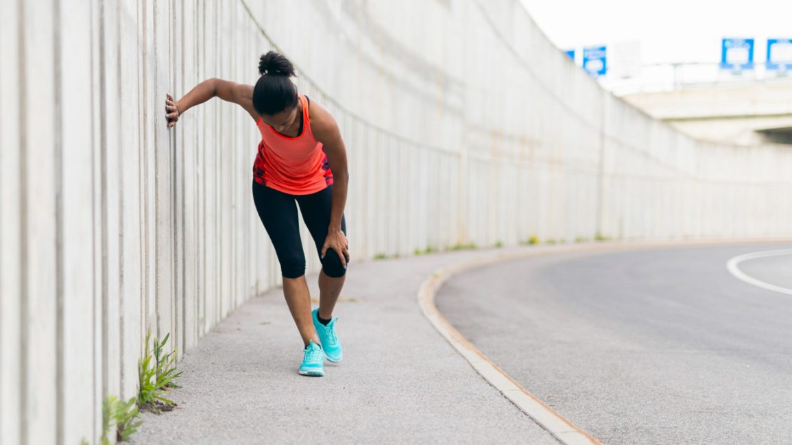 A runner bends over next to a road, holding their injured knee.