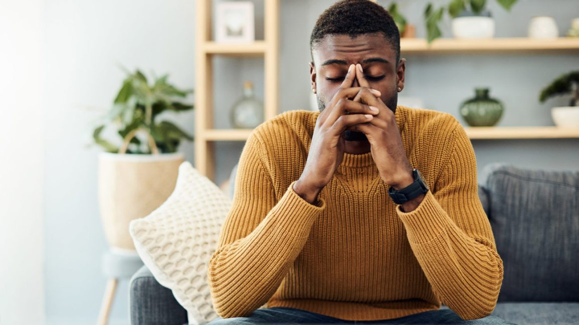 A man sits on a couch, with his fingers pressed against his nose to help alleviate his headache.