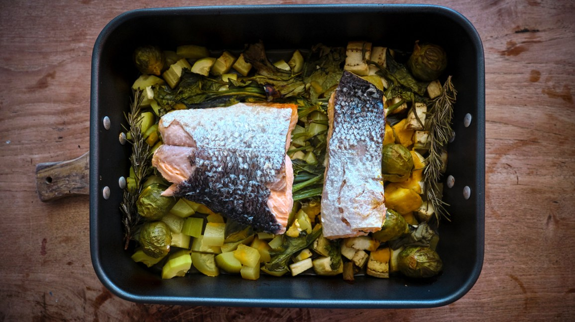 a tray of baked vegetables and salmon