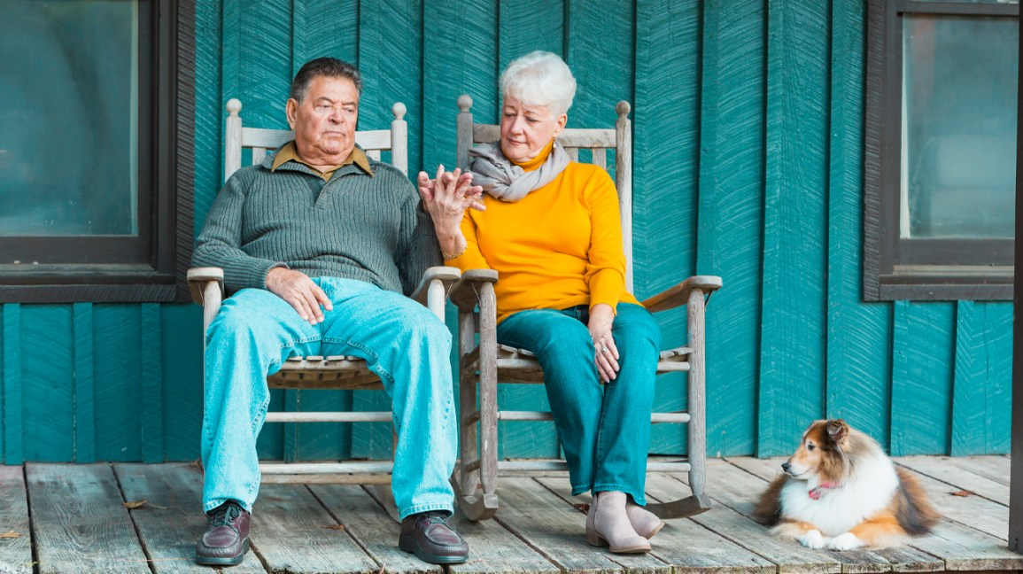 senior man and senior woman sitting on a porch and holding hands next to a dog