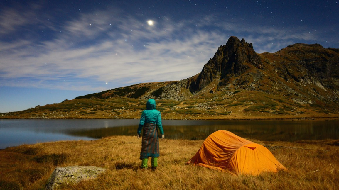 person looking at the stars outside next to tent