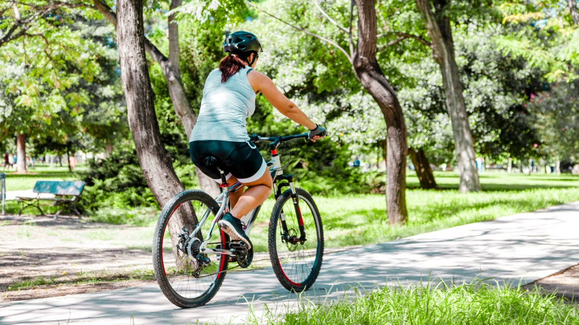 A woman rides a bicycle along a biking trail in a park.