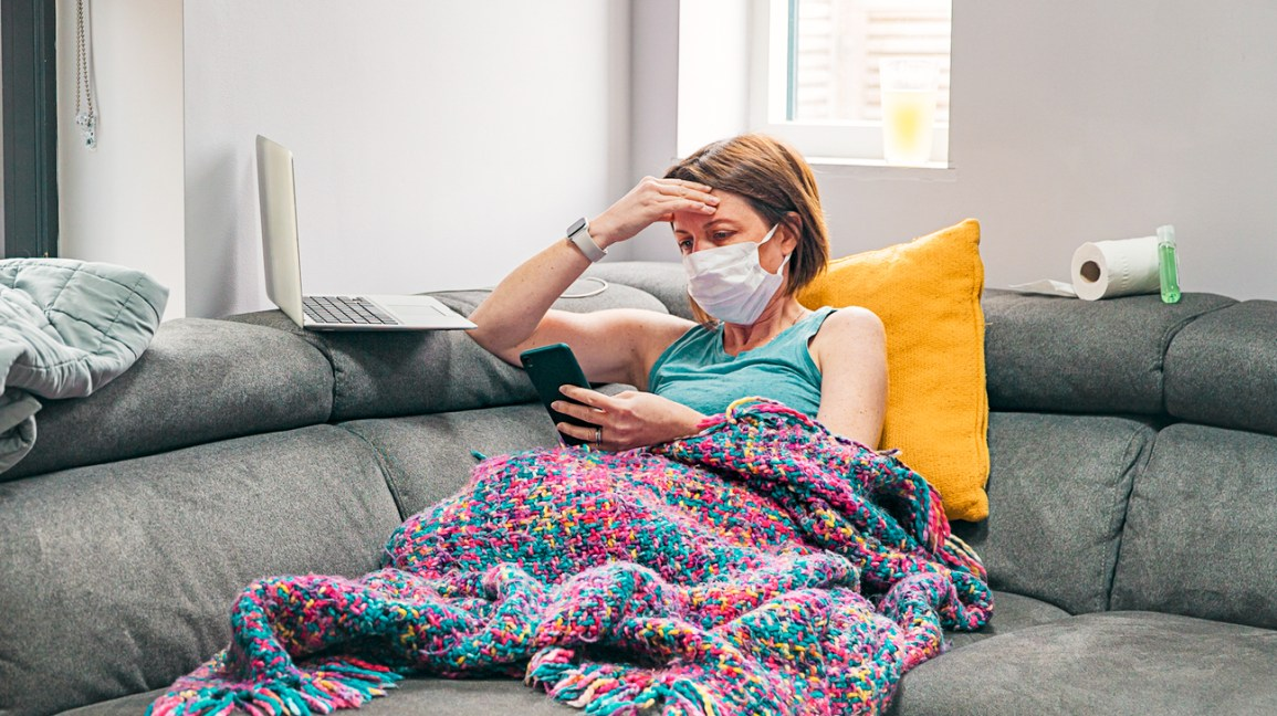 A woman with covid-19 symptoms sits on her couch, wearing a mask with a blanket over her legs.