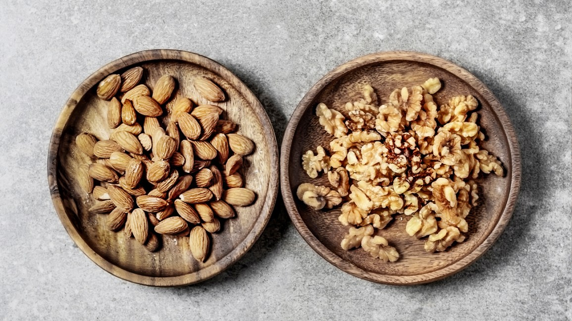 One bowl with almonds and one bowl with walnuts