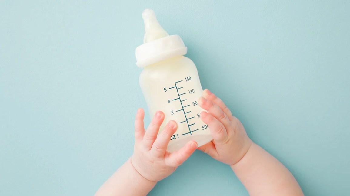 bebê segurando mamadeira