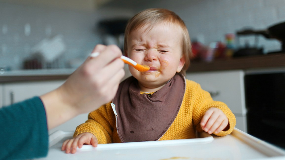 Bambino arrabbiato per il genitore che offre cibo
