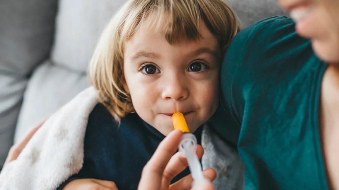 Bambino che prende farmaci liquidi attraverso la siringa