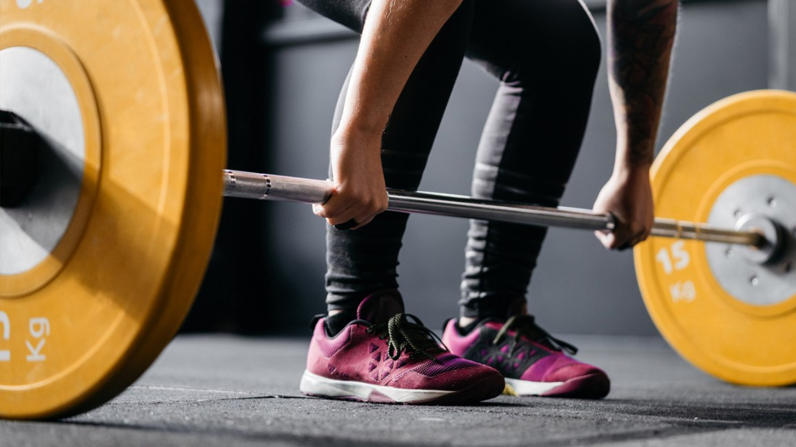 cropped image of a person bending down to pickup a dumbbell barbell