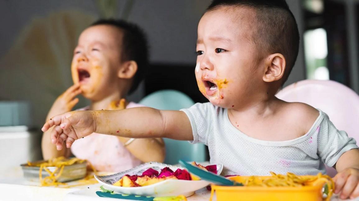gemelli che piangono durante il pasto