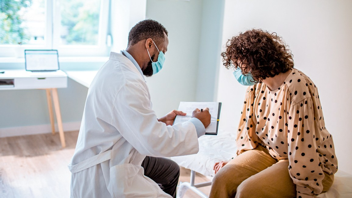 A patient meets with a doctor in the doctor's office.