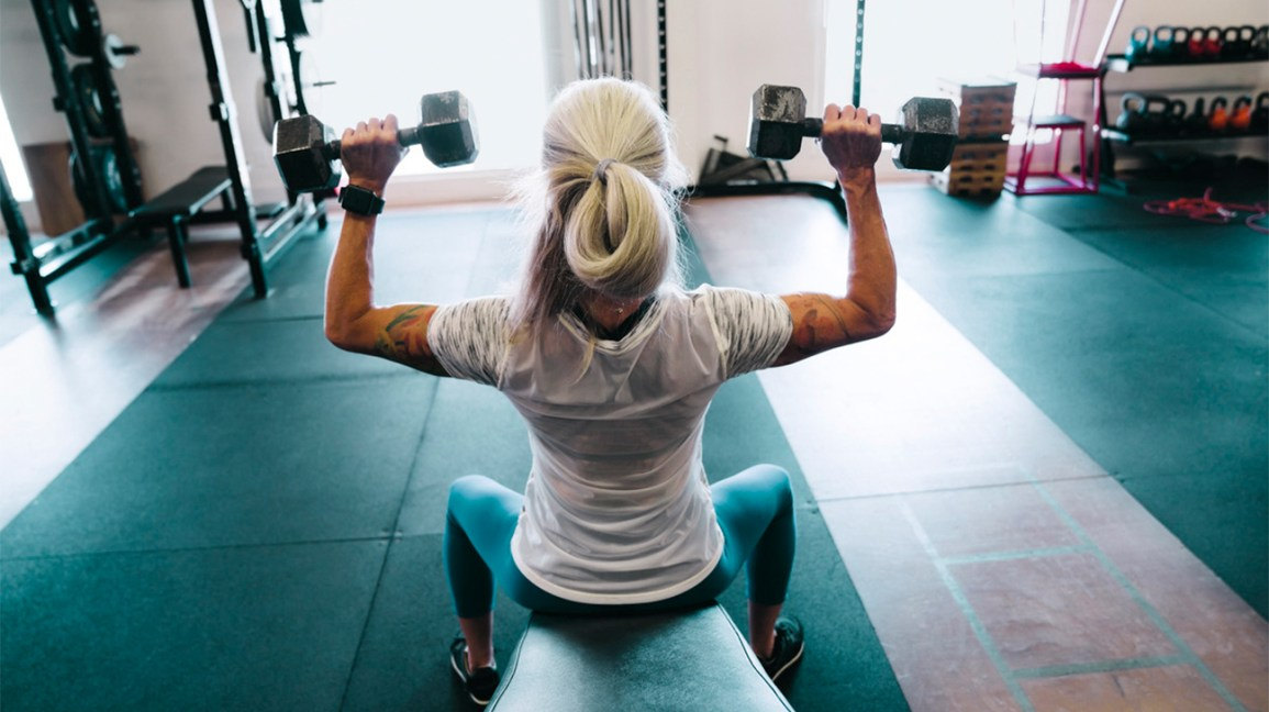 A woman works out in a gym with dumbbells in both hands.