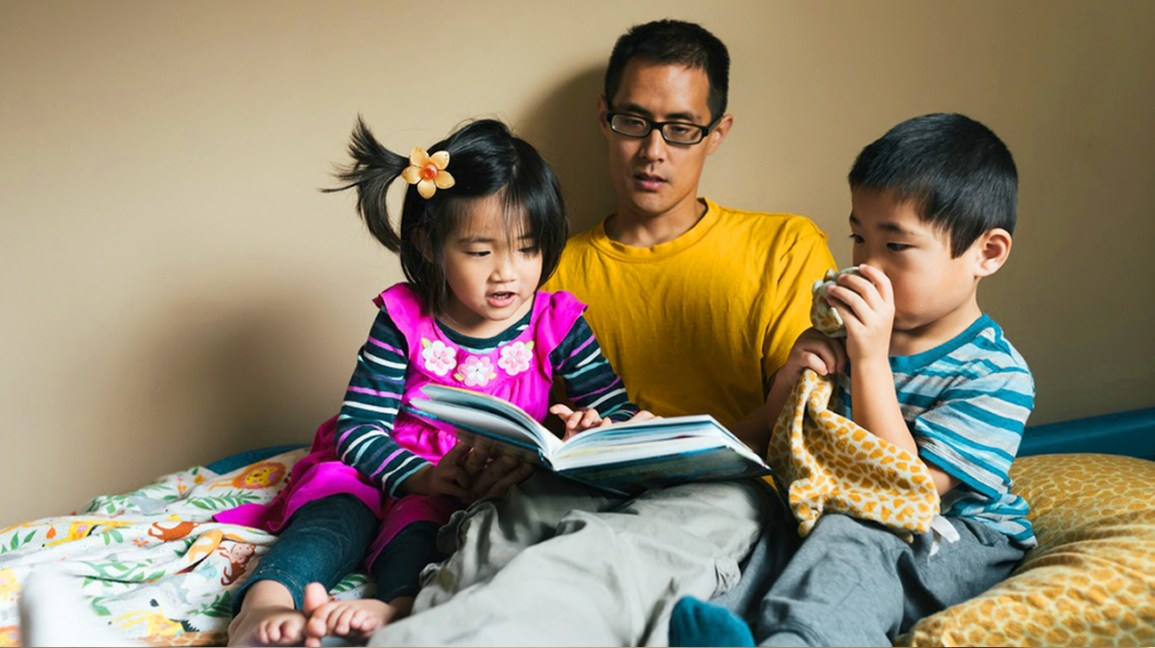 man reading with twins