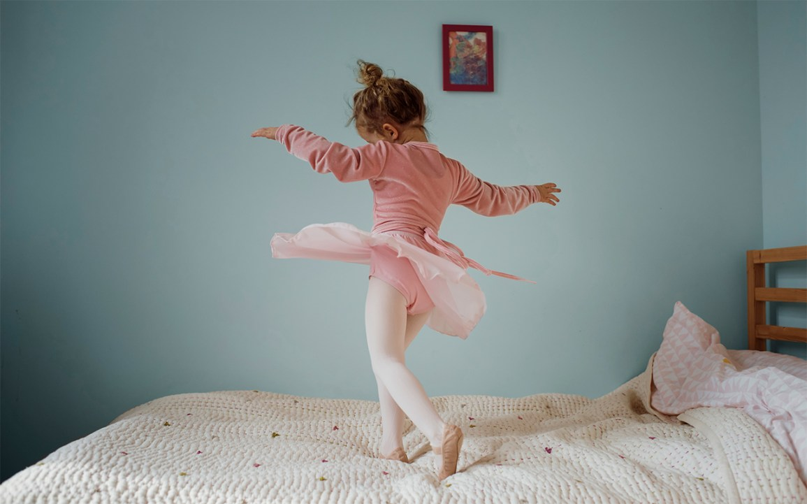 little girl dancing on bed alone