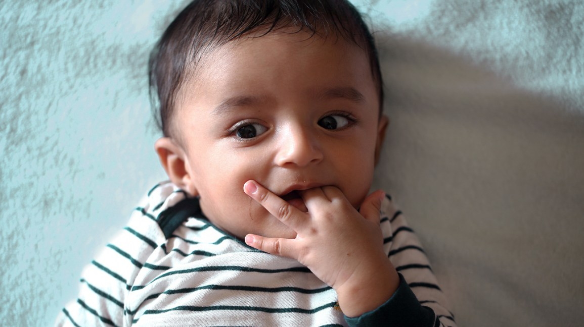 baby with fingers in mouth sign baby is hungry