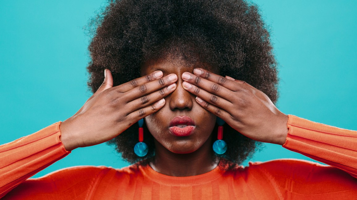 Mulher cobrindo os olhos com as mãos