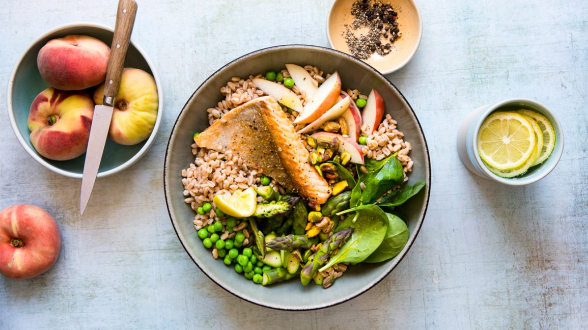 whole-grain bowl with veggies, salmon, and peaches