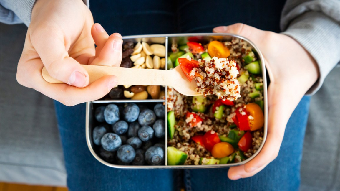 a forkful of quinoa salad with a compartmentalized lunch box