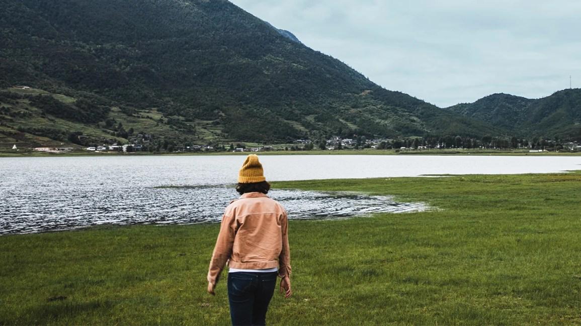 mulher de moletom cor de pêssego e gorro amarelo caminhando no pântano