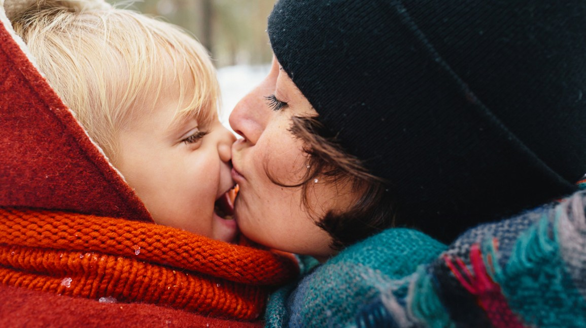 baby in winter clothes gets kiss from mom