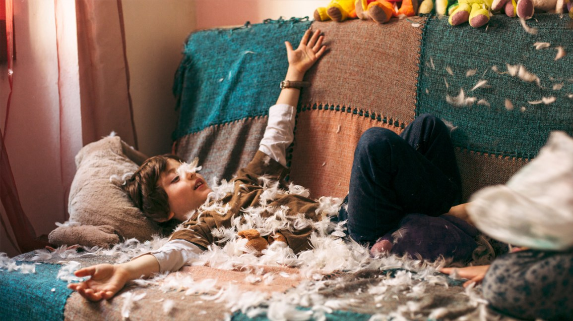 strong willed child plays in feathers from pillow
