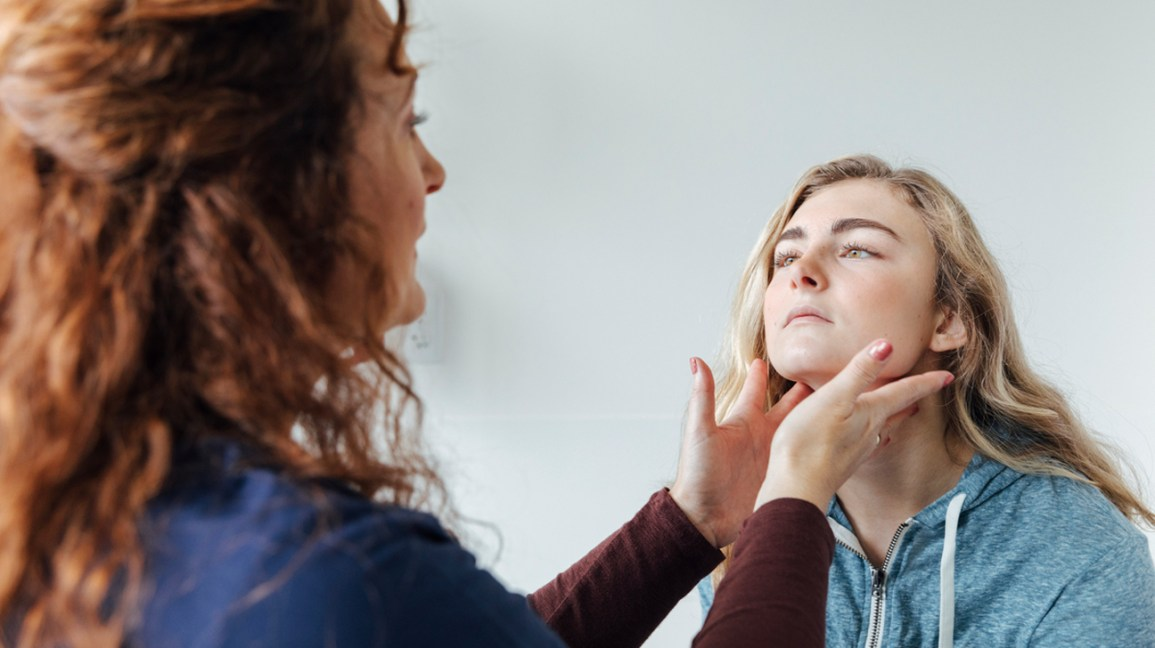 A nurse feels the sore throat of a young female patient.