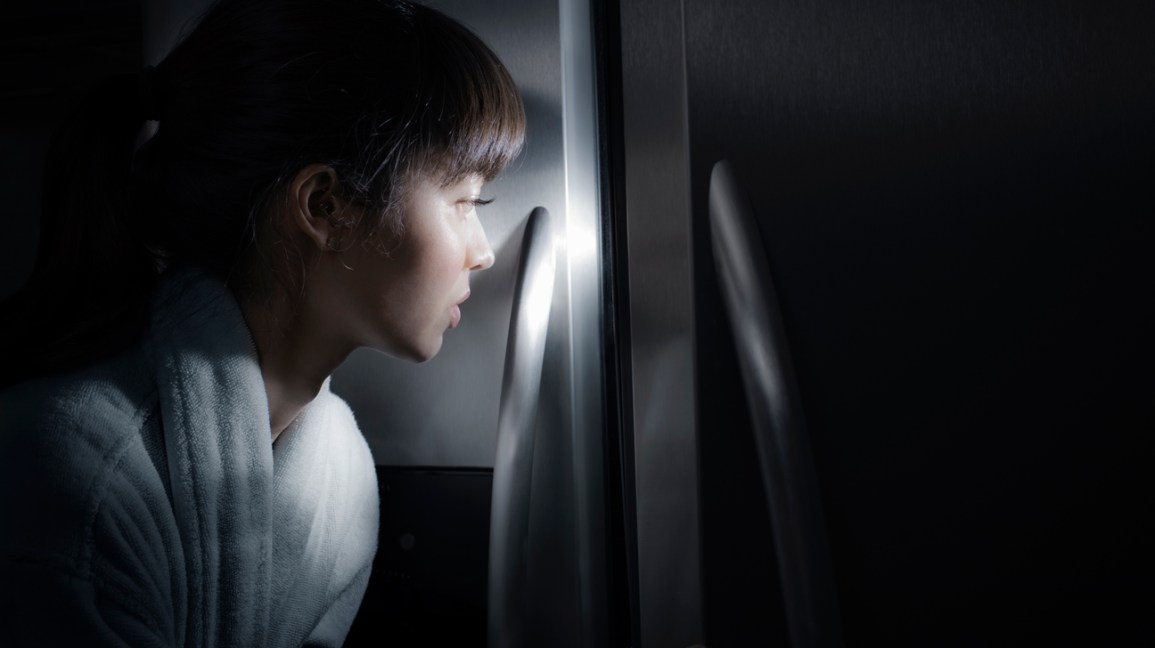 A young woman approaches a refrigerator in a darkened kitchen while sleepwalking.