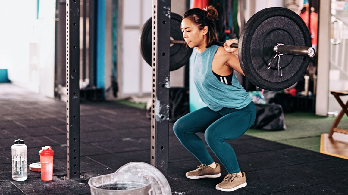 una donna concentrata sul fare uno squat con bilanciere, tiene il peso sulle spalle