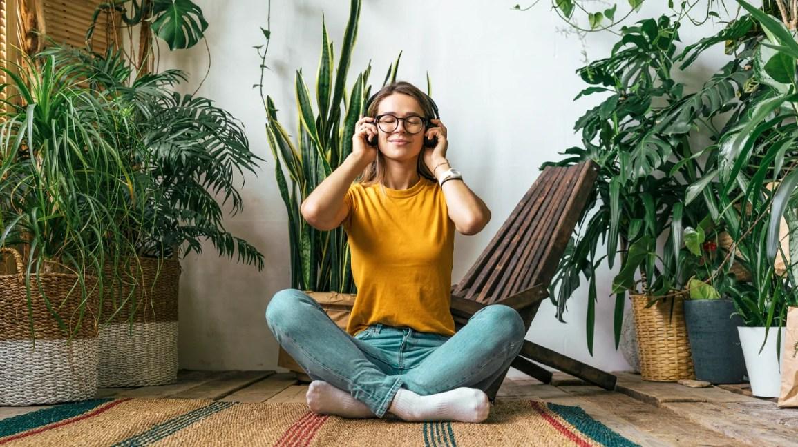 wanita yang memakai headphone duduk di lantai