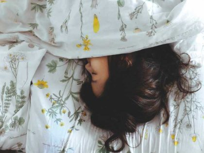 View of woman with dark hair asleep in floral sheets