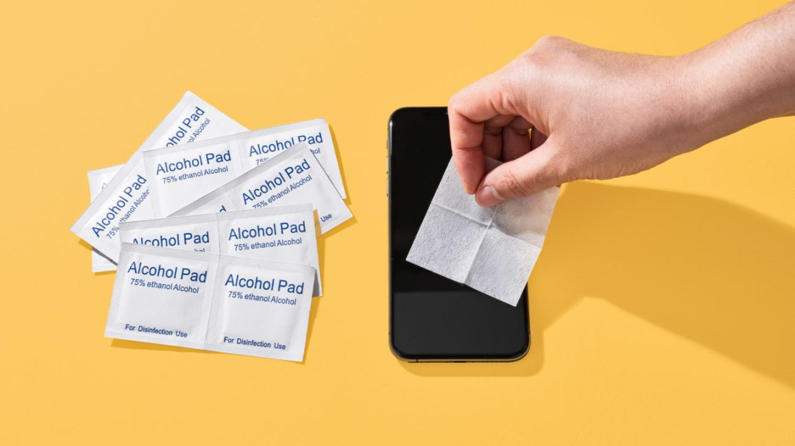 A person cleans their phone, which is lying on a yellow tabletop, with an alcohol wipe.