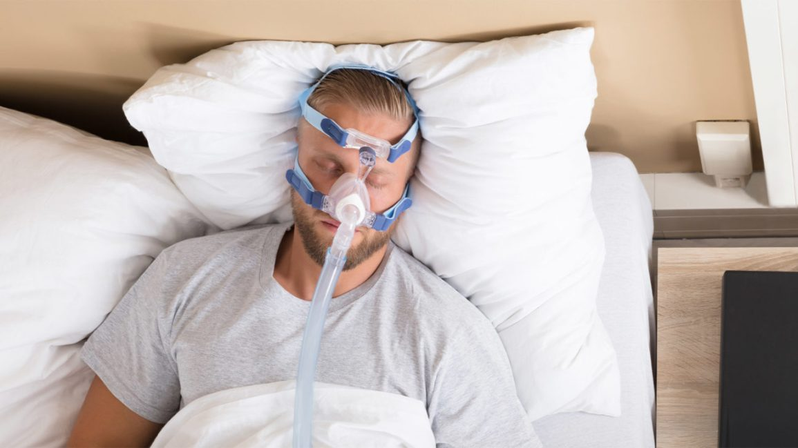 A man lies on his back in bed with a CPAP mask on his face.