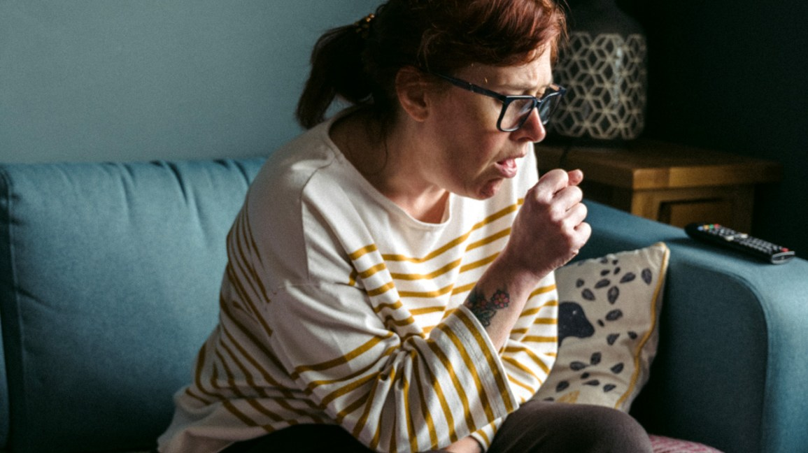 A woman sits on a couch, with her hand in front of her mouth while coughing.