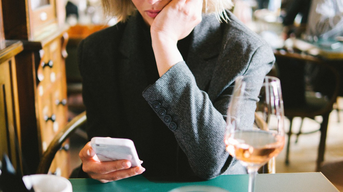 A woman sits at a table in a restaurant, with a glass of wine next to her while she checks her phone.