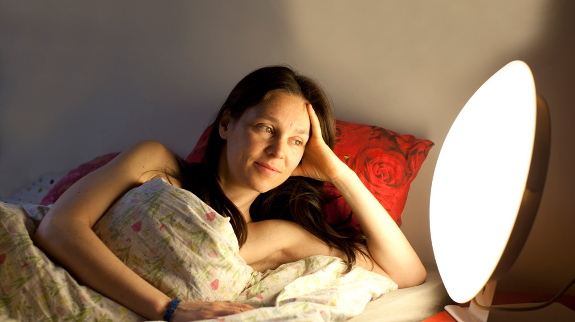 A woman lies  in bed with a light box next to her.