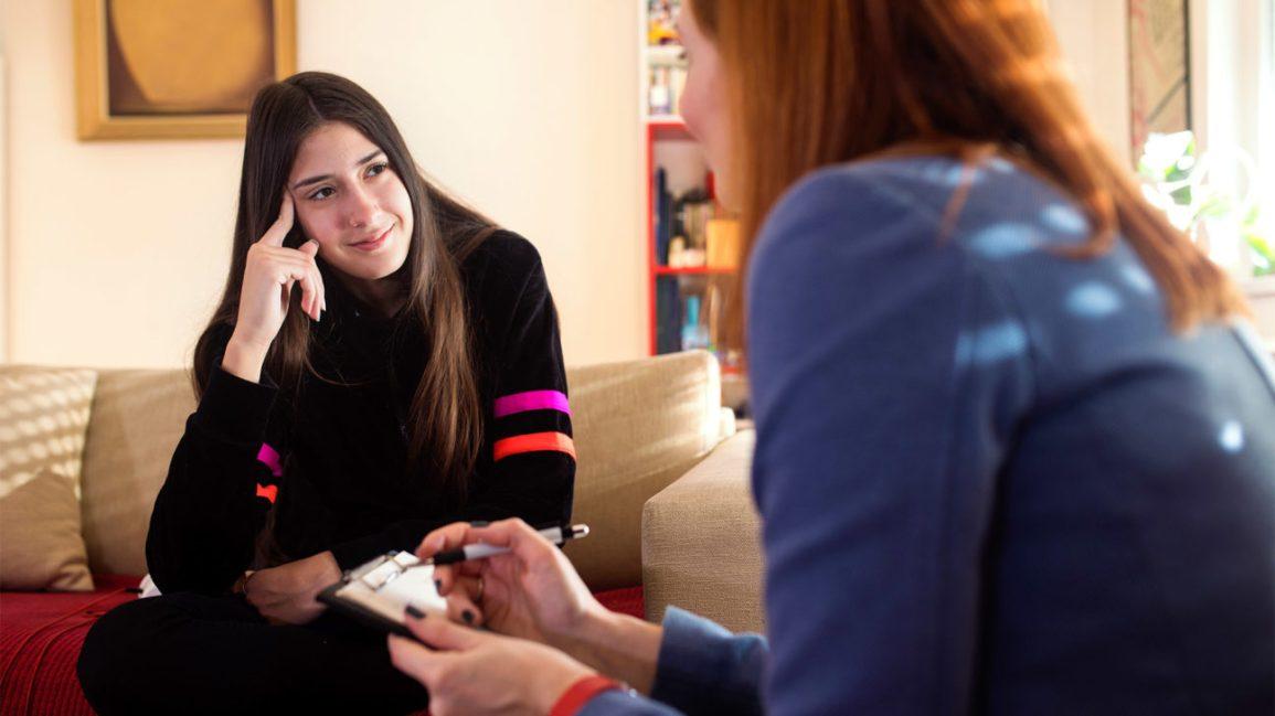 Uma paciente se senta em um sofá enquanto fala com seu terapeuta, que está interagindo com ela e fazendo anotações.