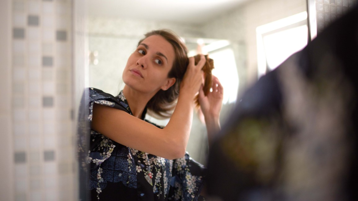 Woman looking at herself in mirror and doing her hair
