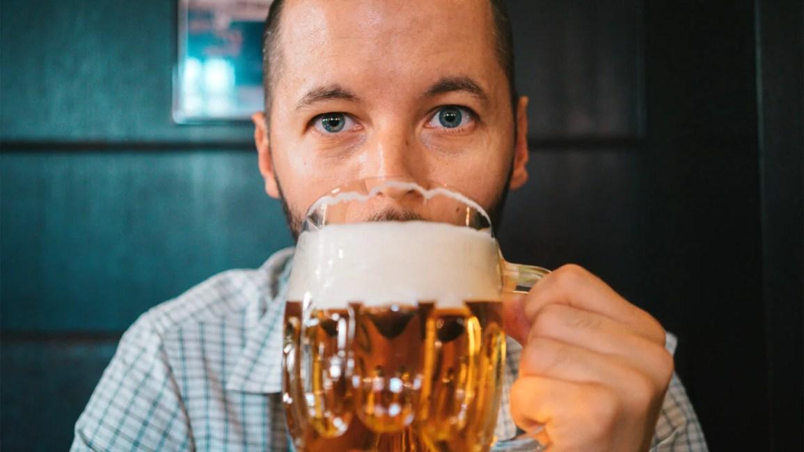 close de um homem segurando uma caneca grande de cerveja
