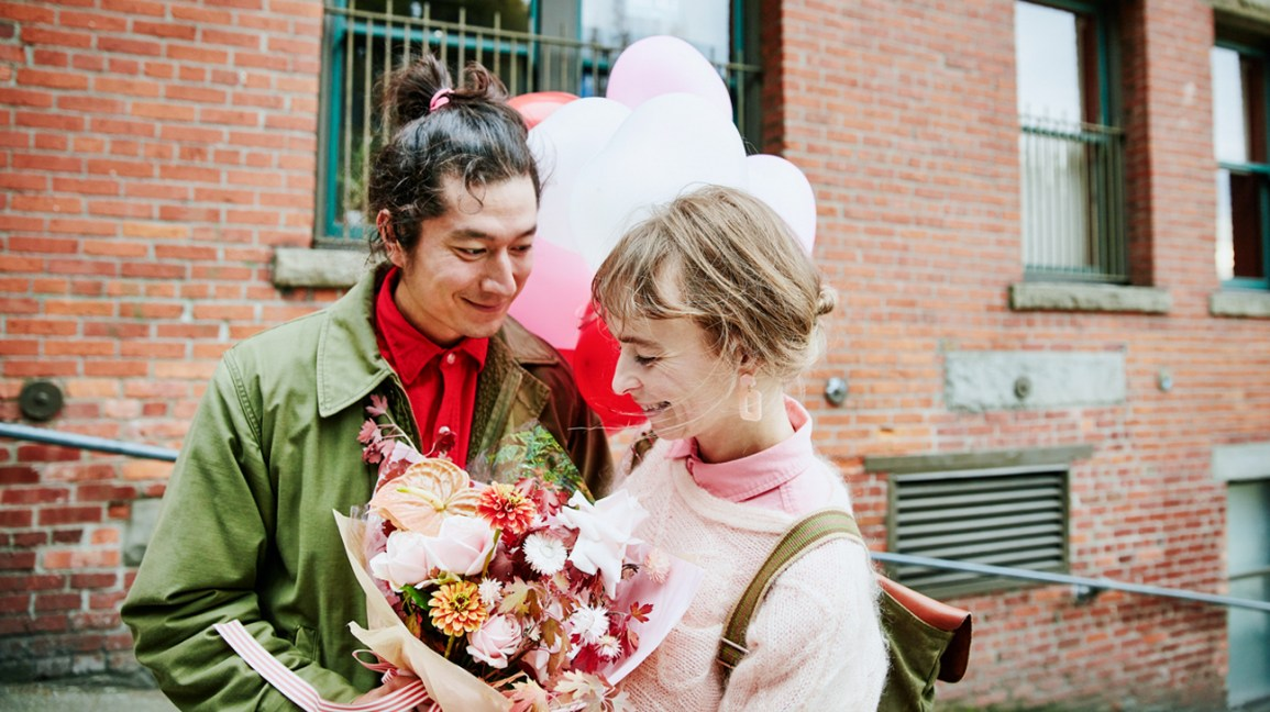 woman holding baloons and flowers from boyfriend